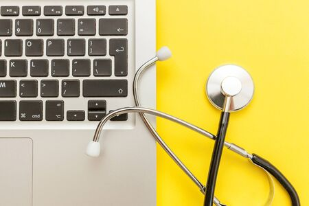 Stethoscope keyboard laptop computer isolated on yellow background. Modern medical Information technology and sofware advances concept. Computer and gadget diagnostics and repair. Flat lay top view