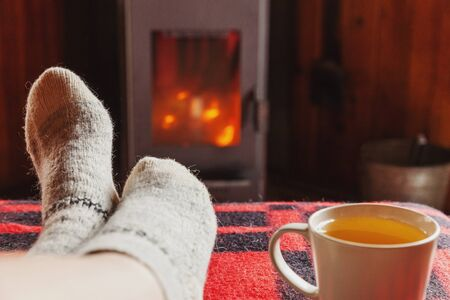Feet legs in winter clothes wool socks and cup tea at fireplace background. Woman sitting at home on winter or autumn evening relaxing and warming up. Winter and cold weather concept. Hygge Christmas eve Imagens