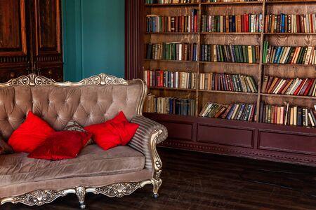Interni classici di lusso della biblioteca domestica. Soggiorno con libreria, libri, poltrona, divano e caminetto. Arredamento pulito e moderno con mobili eleganti. L'istruzione legge il concetto di saggezza dello studio