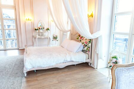 Beautiful luxury classic white bright clean interior bedroom in baroque style with king-size bed, large window, armchair and flower composition Standard-Bild