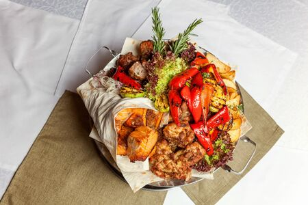 Mixed grill meat, fried vegetables and grilled salmon fish fillets decoration in warm dish. Assorted delicious grilled kebab served with herbs on platter. Restaurant menu plate