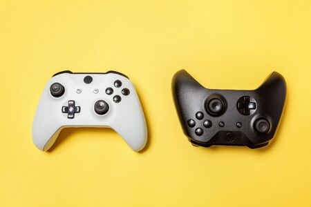 White and black two joystick gamepad, game console on yellow colourful trendy modern fashion pin-up background. Computer gaming competition videogame control confrontation concept. Cyberspace symbol Фото со стока