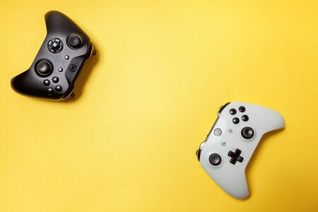 White and black two joystick gamepad, game console on yellow colourful trendy modern fashion pin-up background. Computer gaming competition videogame control confrontation concept. Cyberspace symbol Imagens