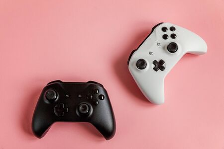 White and black two joystick gamepad, game console on pastel pink colourful trendy pin-up background. Computer gaming competition videogame control confrontation concept. Cyberspace symbol