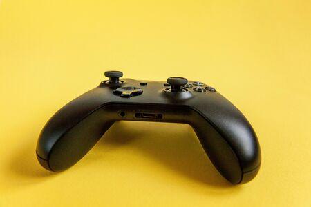 Schwarzes Joystick-Gamepad, Spielkonsole auf gelbem, buntem, trendigem, modernem Pin-up-Hintergrund. Konfrontationskonzept für Computerspiele-Wettbewerbs-Videospiele. Cyberspace-Symbol