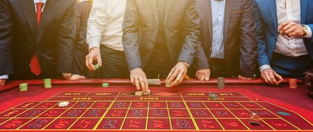 Group of people behind roulette gambling table in luxury casino. Friends playing poker at roulette table with tape measure. Vegas games nightlife lucky winning concept. Banner Zdjęcie Seryjne - 133457481