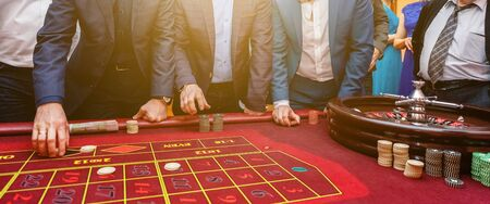 Group of people behind roulette gambling table in luxury casino. Friends playing poker at roulette table with tape measure. Vegas games nightlife lucky winning concept. Banner 写真素材