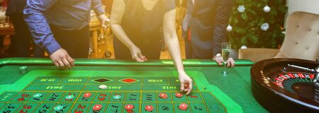 Group of people behind roulette gambling table in luxury casino. Friends playing poker at roulette table with tape measure. Vegas games nightlife lucky winning concept. Banner Zdjęcie Seryjne - 133457500