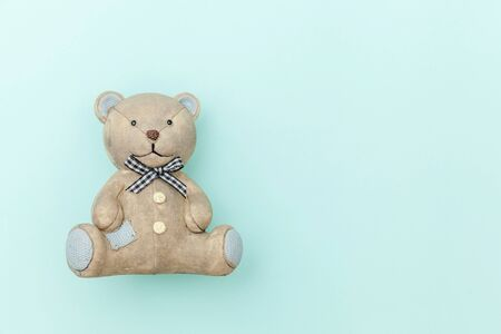 Simply minimal design toy bear isolated on pastel blue background. Children care materinity family concept. Flat lay top view copy space