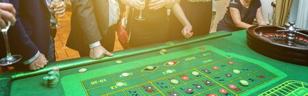 Group of people behind roulette gambling table in luxury casino. Friends playing poker at roulette table with tape measure. Vegas games nightlife lucky winning concept. Banner 版權商用圖片