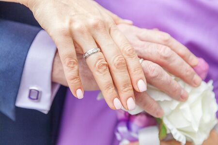 Bride and groom hands with wedding rings against background of bridal bouquet of flowers. Declaration of love, spring. Wedding card, Valentines Day greeting. Wedding rings. Wedding day details Stock Photo
