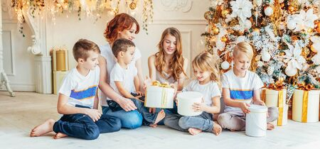 Happy family mother and five children relax playing near Christmas tree on Christmas eve at home. Mom, daughters, sons in light room with winter decoration. New Year time for celebration. Banner Archivio Fotografico