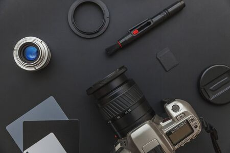 Photographer workplace with dslr camera system, camera cleaning kit, lens and camera accessory on dark black table background. Hobby travel photography concept. Flat lay top view copy space Standard-Bild - 133853340