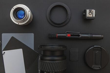 Photographer workplace with dslr camera system, camera cleaning kit, lens and camera accessory on dark black table background. Hobby travel photography concept. Flat lay top view copy space Standard-Bild - 133853342