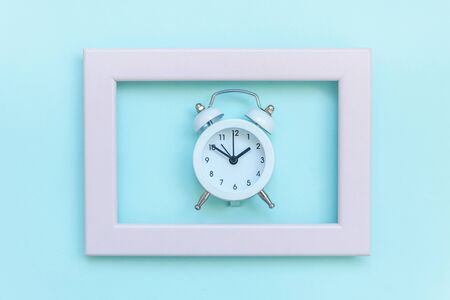 Ringing twin bell vintage alarm clock in pink frame isolated on blue pastel colorful trendy background. Rest hours time of life good morning night wake up awake concept. Flat lay top view copy space Stock Photo