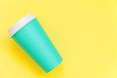 Simply flat lay design blue paper coffee cup isolated on yellow colorful trendy background. Takeaway drink container. Good morning wake up awake concept. Template of drink mockup. Top view copy space 免版税图像