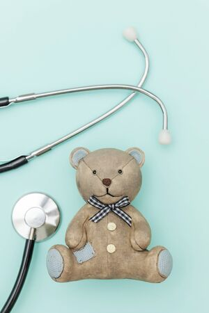 Simply minimal design toy bear and medicine equipment stethoscope isolated on pastel blue background. Health care children doctor concept. Pediatrician symbol. Flat lay top view copy space