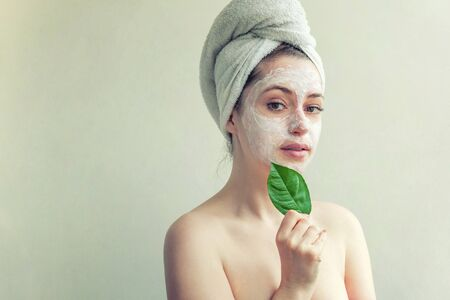 Beauty portrait of woman in towel on head with white nourishing mask or creme on face and green leaf in hand, white background isolated. Skincare cleansing eco organic cosmetic spa concept