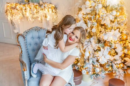 Happy family woman mother and little girl relax playing near Christmas tree on Christmas eve at home. Mom, daughter in light bedroom with winter decoration. Christmas New Year time for celebration