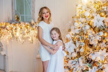 Happy family woman mother and little girl relax playing near Christmas tree on Christmas eve at home. Mom, daughter in light bedroom with winter decoration. Christmas New Year time for celebration Stock Photo - 133854062