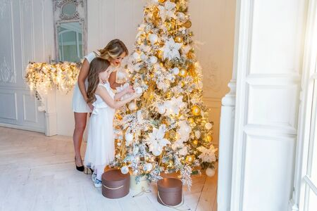 Happy family woman mother and little girl decorating Christmas tree on Christmas eve at home. Mom, daughter in light bedroom with winter decoration. Christmas New Year time for celebration
