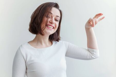 Happy girl smiling. Beauty portrait young happy positive laughing brunette woman showing holding something copyspace in hand on white background isolated. European woman. Positive human emotion Stock fotó