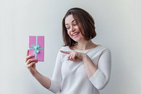 Young positive woman holding small pink gift box isolated on white background. Preparation for holiday. Girl looking happy and excited. Christmas birthday valentine celebration present concept Stock fotó