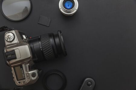 Photographer workplace with dslr camera system, camera cleaning kit, lens and camera accessory on dark black table background. Hobby travel photography concept. Flat lay top view copy space 版權商用圖片
