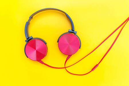 Red headphones on yellow background. Minimalist simple photo of earphones with copy space. Red dj headphones with cable isolated on colorful backdrop, flat lay top view. Music concept
