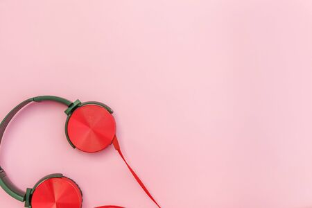 Red headphones on pink background. Minimalist simple photo of earphones with copy space. Red dj headphones with cable isolated on pastel colorful backdrop, flat lay top view. Music concept Standard-Bild