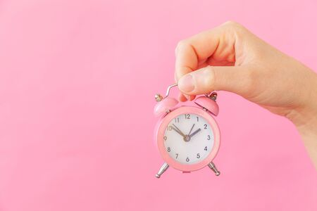 Simply design female woman hand holding ringing twin bell alarm clock isolated on pink pastel colorful trendy background. Rest hours time of life good morning night wake up awake concept. Copy space 写真素材