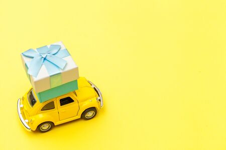 Simply design yellow vintage retro toy car delivering gift box on roof isolated on trendy yellow background. Christmas New Year birthday Valentine's day celebration present romantic concept.