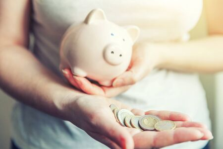 Female woman hands holding pink piggy bank and euro coins. Saving investment budget business wealth retirement financial money banking concept Фото со стока