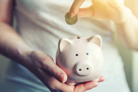 Female woman hands holding pink piggy bank and putting money Euro coin. Saving investment budget business wealth retirement financial money banking concept