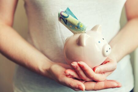 Female woman hands holding pink piggy bank and putting money Euro. Saving investment budget business wealth retirement financial money banking concept