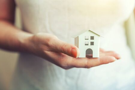 Female woman hands holding small miniature white toy house. Mortgage property insurance dream moving home and real estate concept