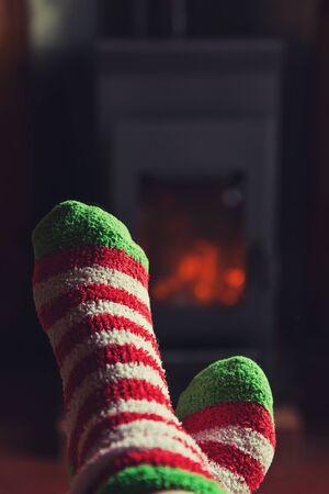 Füße Beine in Winterkleidung Wollsocken am Kamin Hintergrund. Frau, die am Winter- oder Herbstabend zu Hause sitzt und sich entspannt und aufwärmt. Konzept für Winter und kaltes Wetter. Hygge Heiligabend