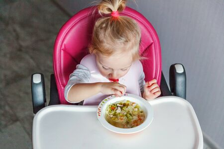 Infant baby with dirty face eating soup herself with spoon. Cute little girl sitting in high baby chair in kitchen at home. Maternity family childhood concept