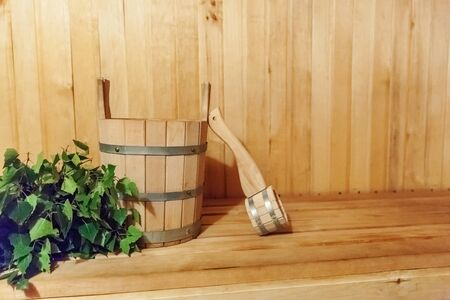 Interior details Finnish sauna steam room with traditional sauna accessories basin birch broom scoop. Traditional old Russian bathhouse SPA Concept. Relax country village bath concept