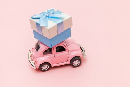 Simply design pink vintage retro toy car delivering gift box on roof isolated on trendy pastel pink background. Christmas New Year birthday Valentine's day celebration present romantic concept. Reklamní fotografie
