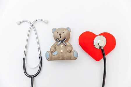 Simply minimal design toy bear red heart and medicine equipment stethoscope isolated on white background. Health care children doctor concept. Pediatrician symbol. Flat lay top view copy space