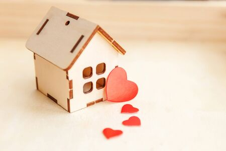 Miniature toy model house with red heart on wooden backdrop. Eco Village, abstract environmental background. Real estate mortgage property sweet dream home ecology concept