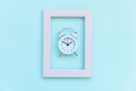 Ringing twin bell vintage alarm clock in pink frame isolated on blue pastel colorful trendy background. Rest hours time of life good morning night wake up awake concept. Flat lay top view copy space 写真素材