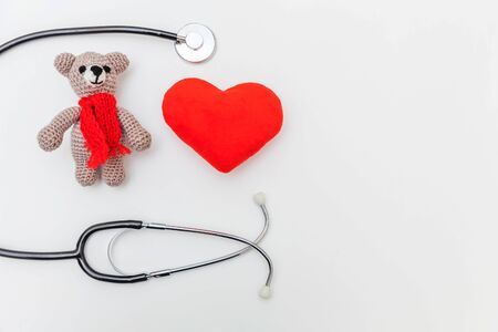 Simply minimal design toy bear red heart and medicine equipment stethoscope isolated on white background. Health care children doctor concept. Pediatrician symbol. Flat lay top view copy space Zdjęcie Seryjne