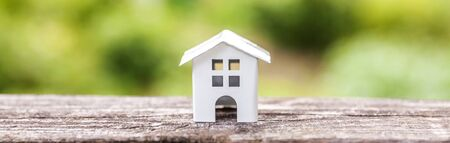 Miniature white toy model house in wooden background near green backdrop. Eco Village, abstract environmental background. Real estate mortgage property insurance dream home ecology concept Banner