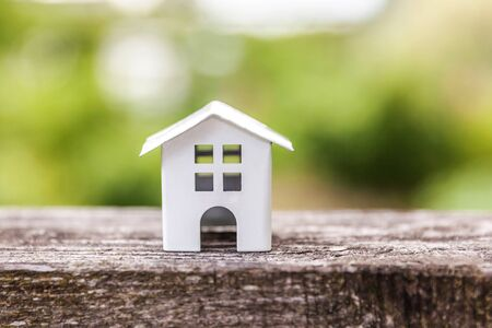 Miniature white toy model house in wooden background near green backdrop. Eco Village, abstract environmental background. Real estate mortgage property insurance dream home ecology concept Zdjęcie Seryjne