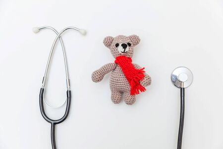 Simply minimal design toy bear and medicine equipment stethoscope isolated on white background. Health care children doctor concept. Pediatrician symbol. Flat lay top view copy space