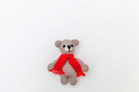 Simply minimal design with toy bear in red scarf isolated on white background. Children care materinity family concept. Flat lay top view copy space