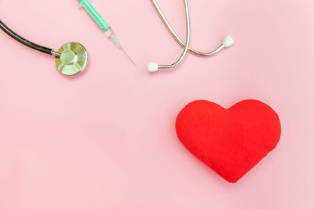 Simply minimal design with medicine equipment stethoscope or phonendoscope syringe and red heart isolated on trendy pastel pink background. Instrument device for doctor. Health care life insurance concept
