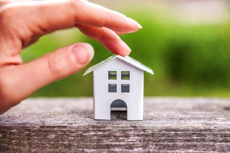 Miniature model house in wooden background near green backdrop and female woman hand. Eco Village, abstract environmental background. Real estate mortgage property insurance dream home ecology concept Zdjęcie Seryjne